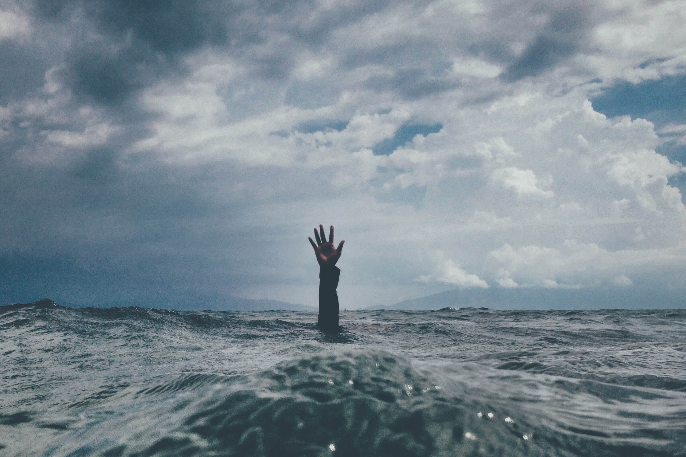 person drowning with hands above the water