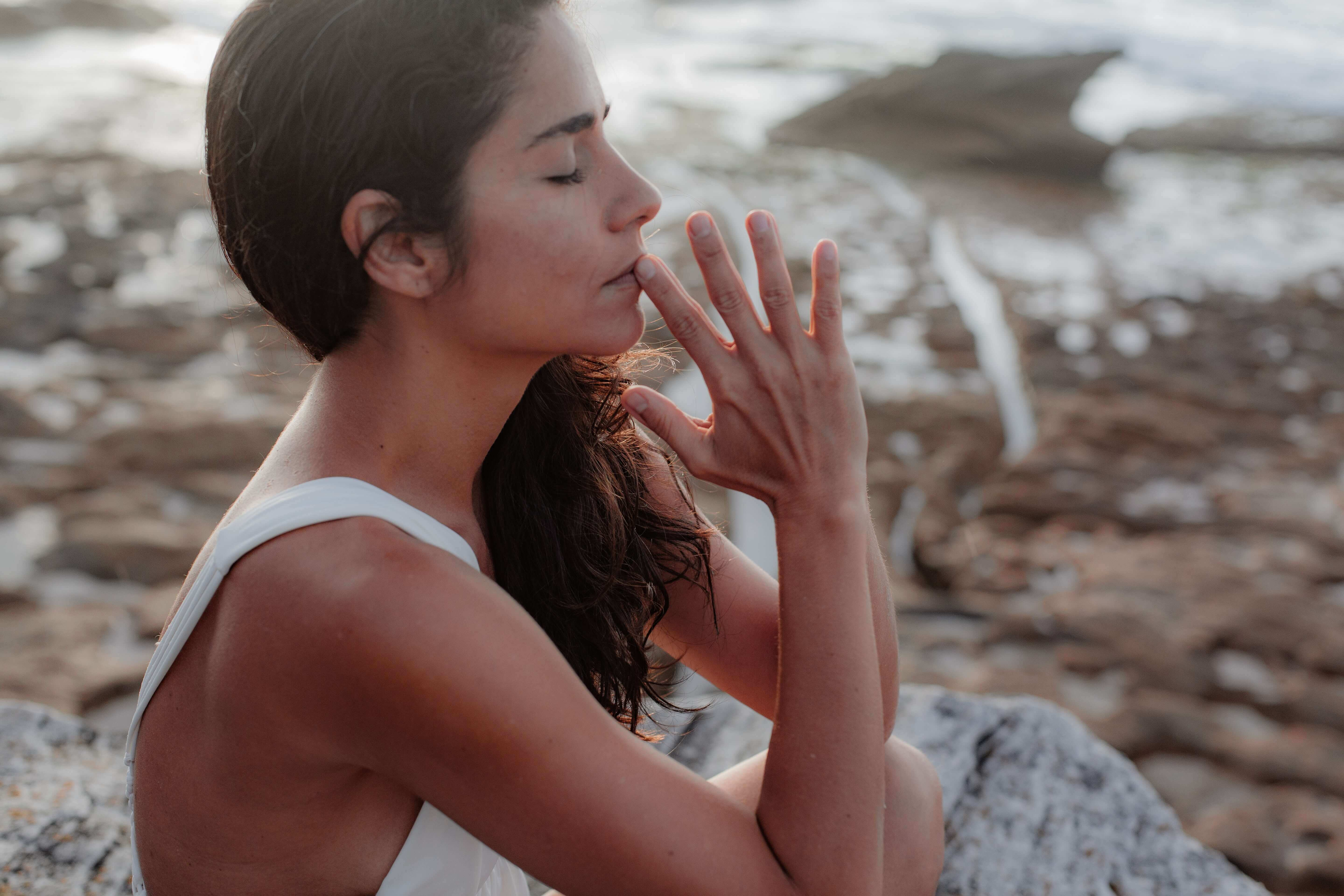 woman wearing white tank top meditating
