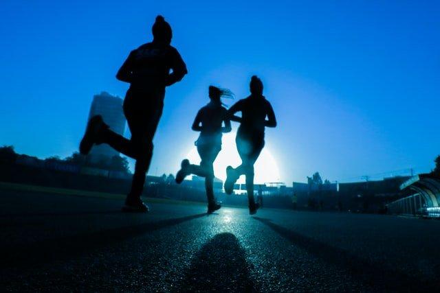 silhouette of three women running