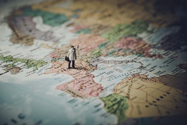 small man figure walking on a map