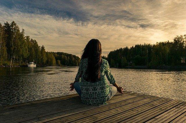 lady sitting on a wood near a lake