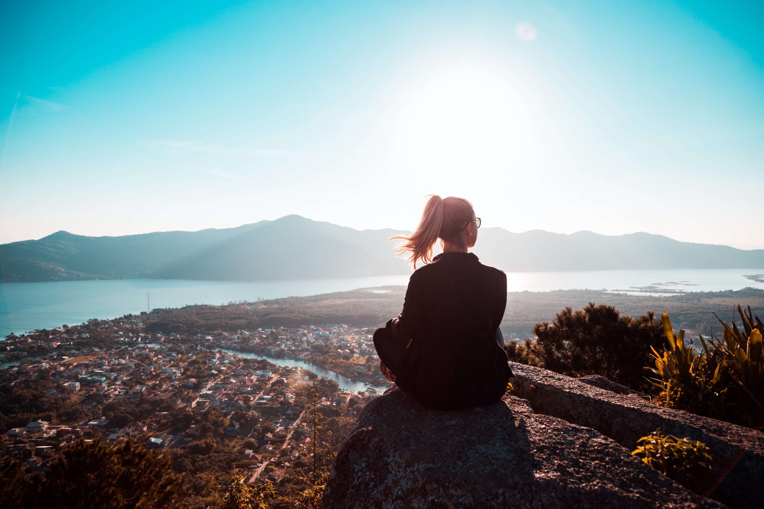 woman sitting alone above the mountain