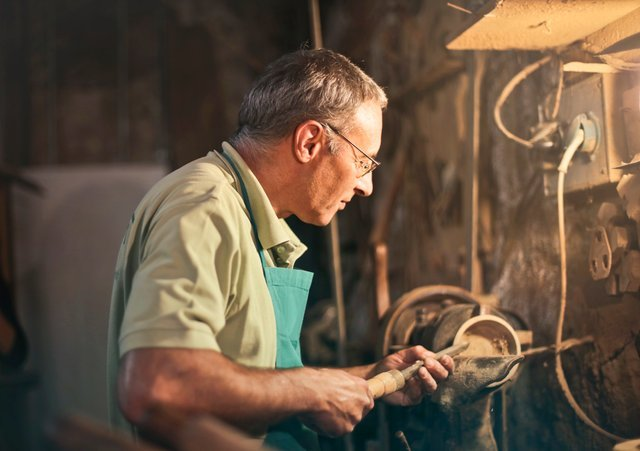man working on a lathe machine in a workshop