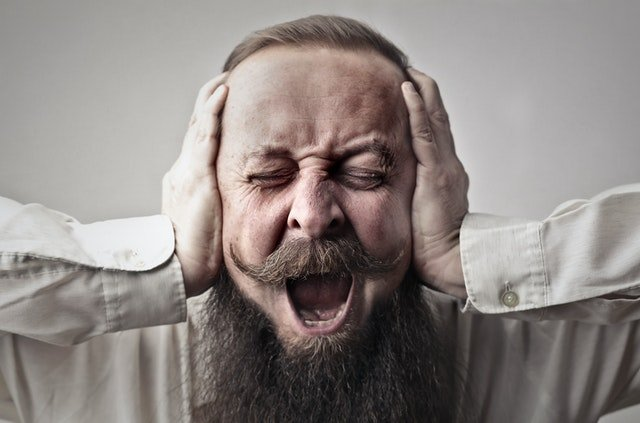 Screaming Man With a Full Beard Covering His Ears and Closing His Eyes