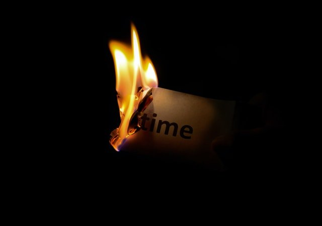 burning piece of paper with time written on it
