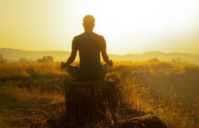 man sitting meditating facing the sunset