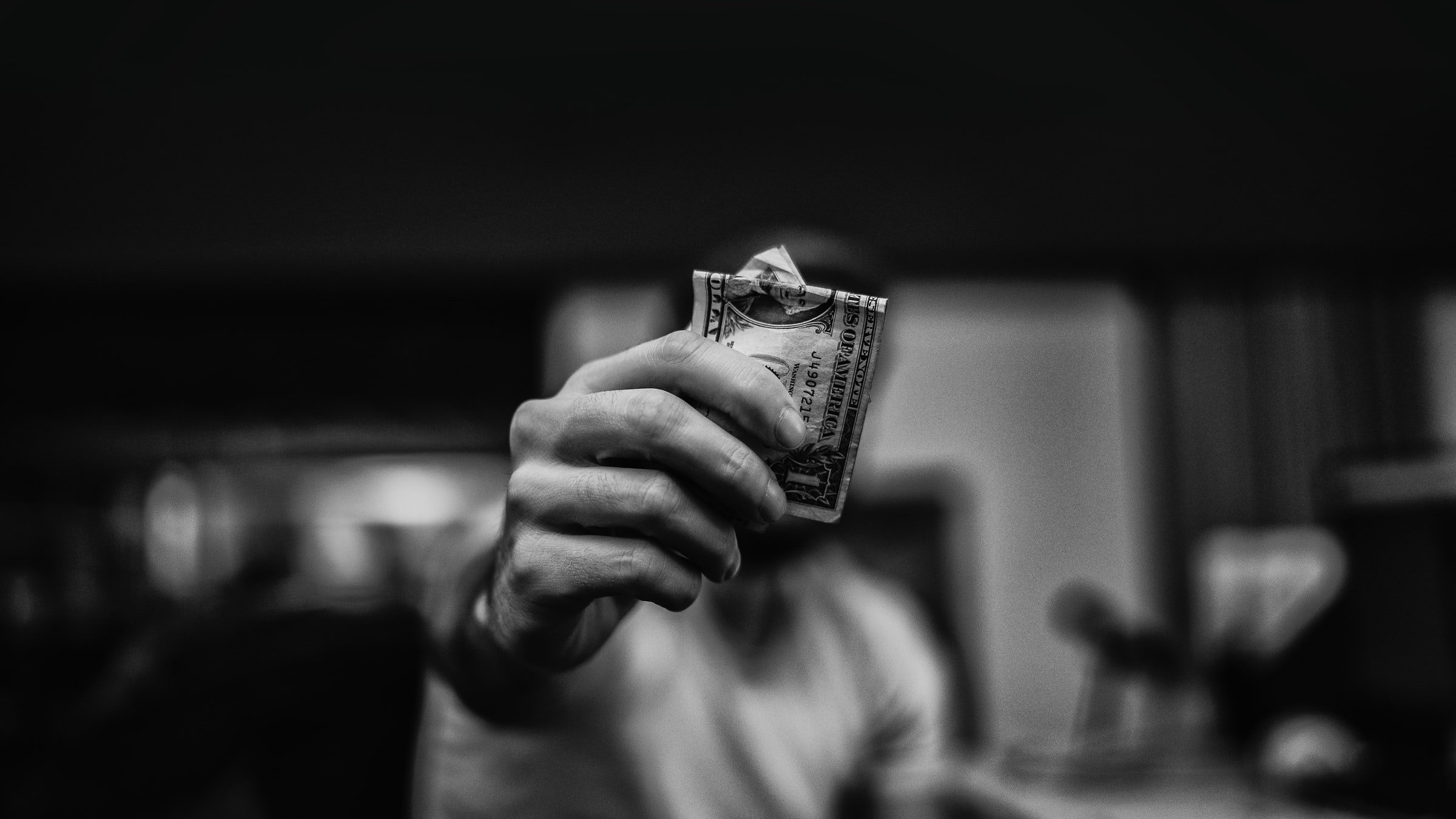 man holding out a dollar bill