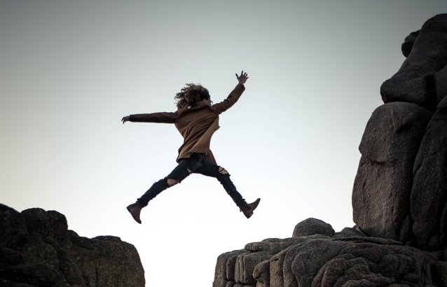 woman jumping on a cliff