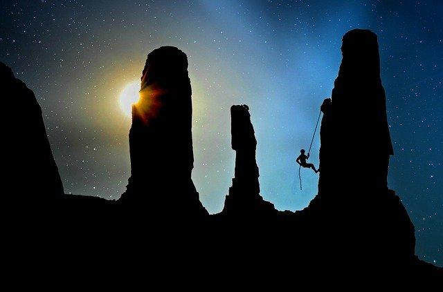 silhouette of a man climbing