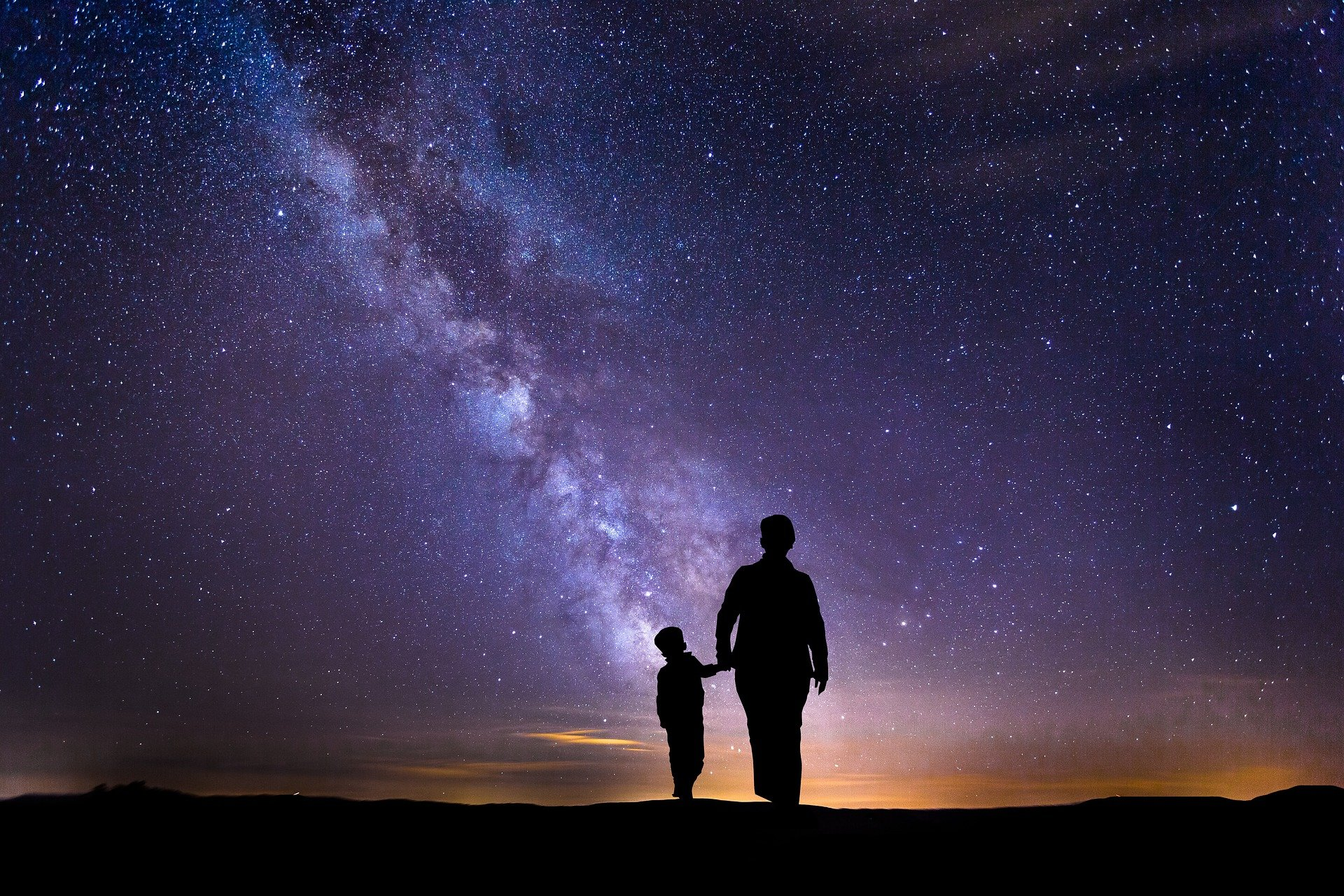 person and a child walking on a dark night under the stars