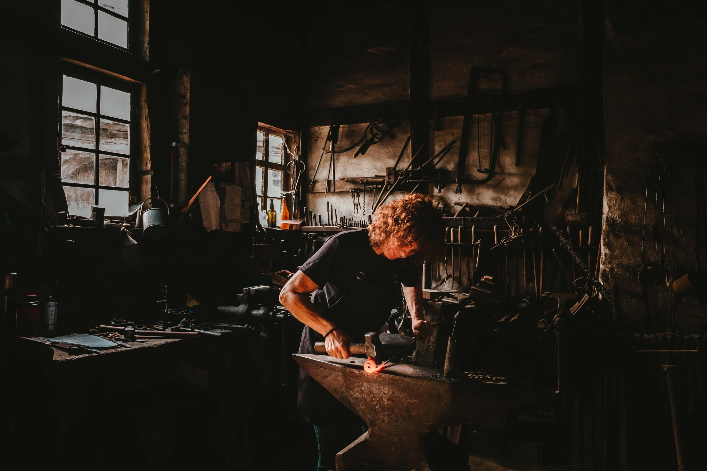man holding a hammer while forging