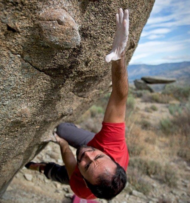 man climbing-on gray concrete peak at daytime