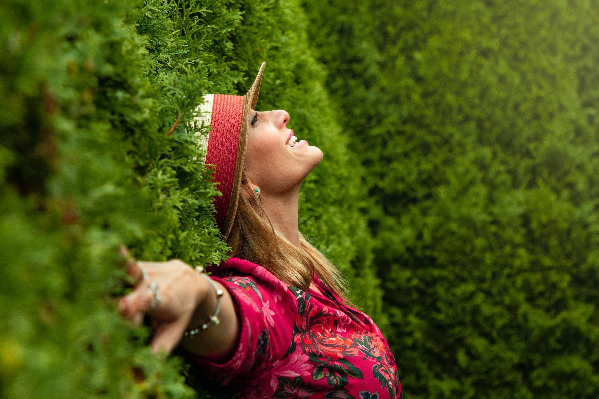 woman leaning on green grass wall