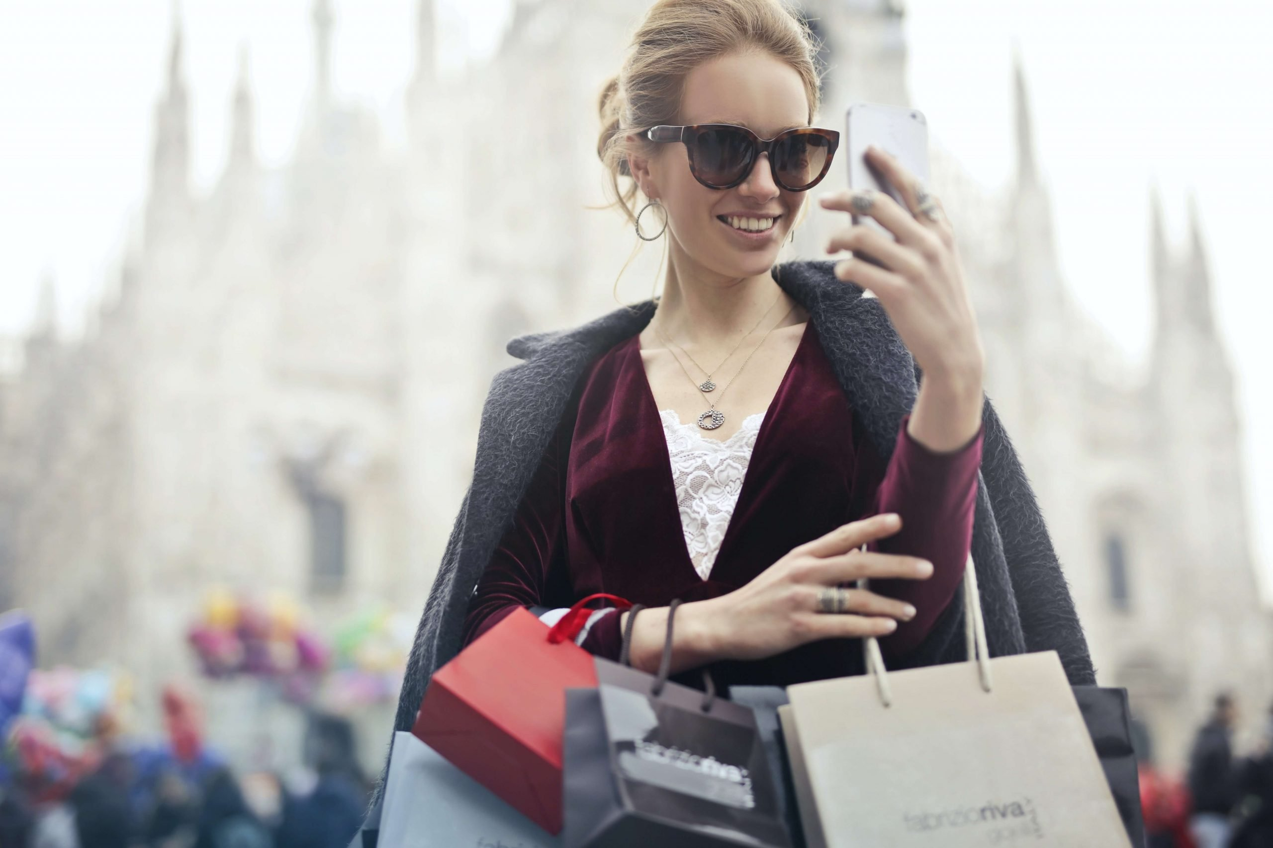 woman with shopping bags holding a phone