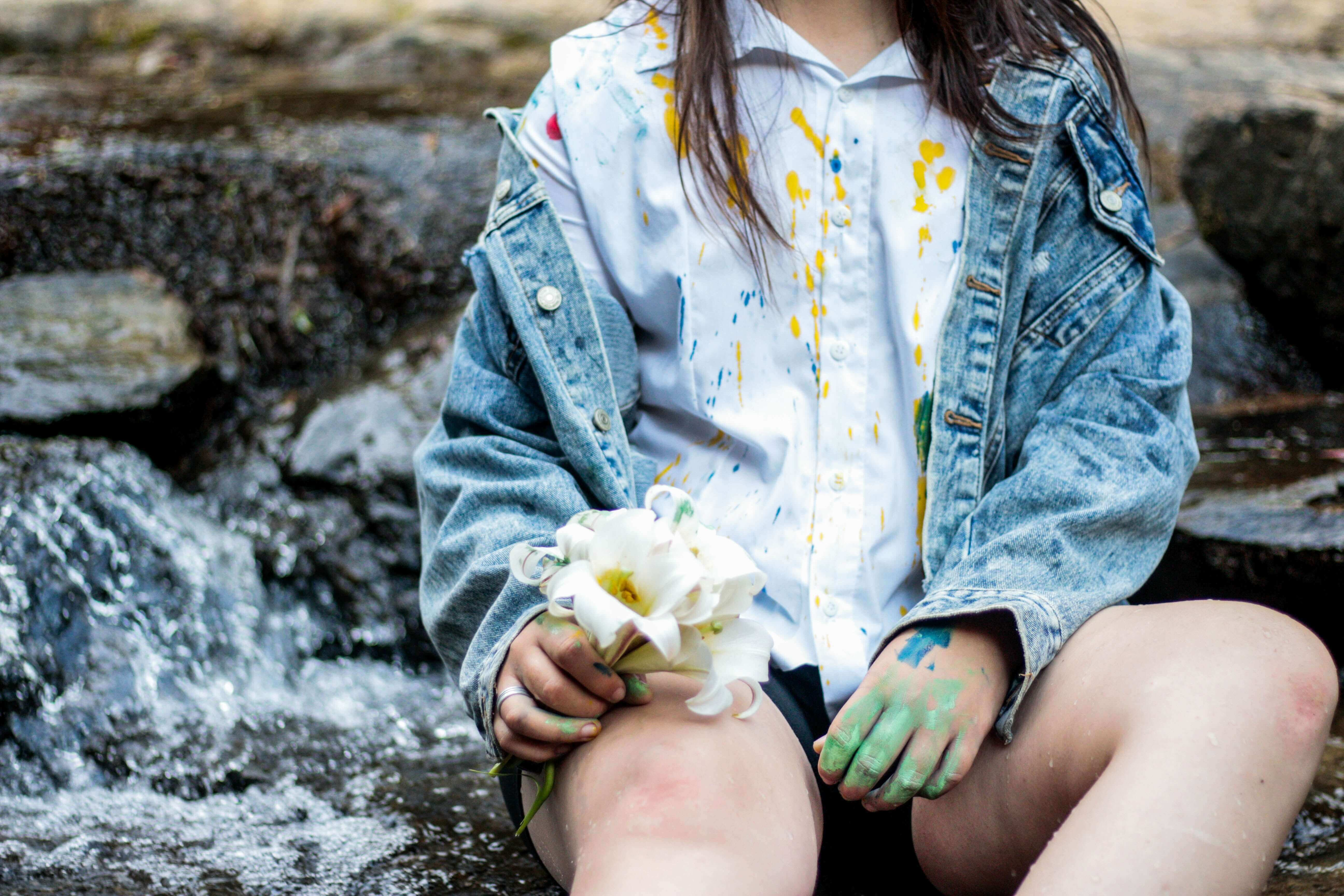girl with messy clothes holding a flower