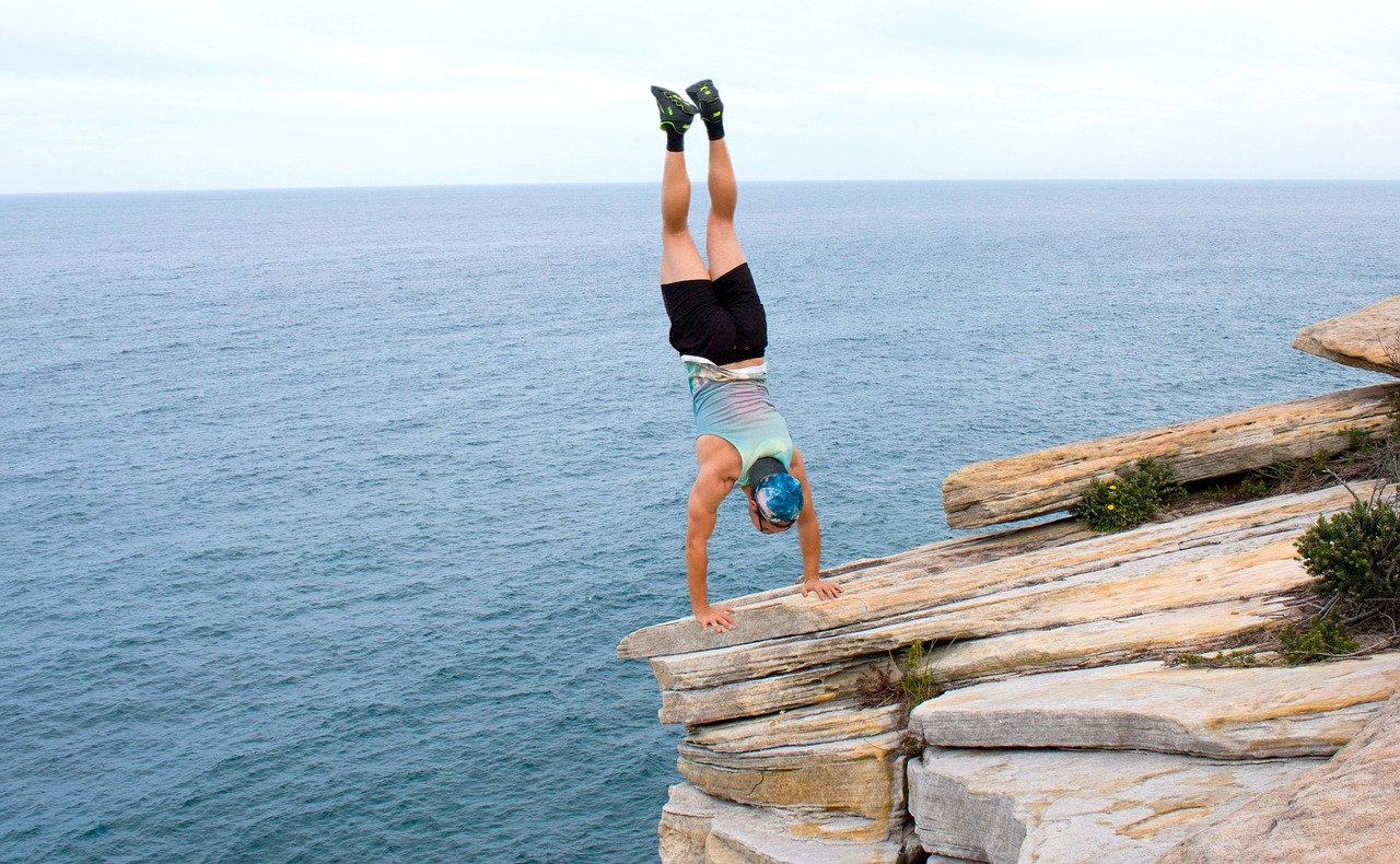 man standing upside down on a cliff