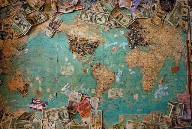 map of the world with dollar bill around it