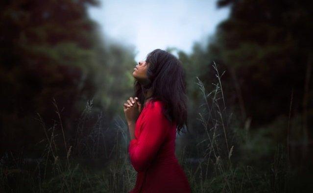 girl in red shirt praying