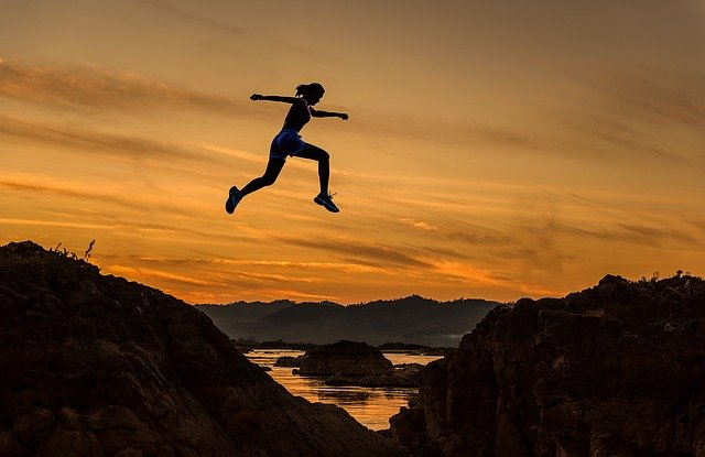 woman jumping from a rock to another