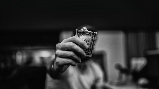 man holding a 1 dollar bill