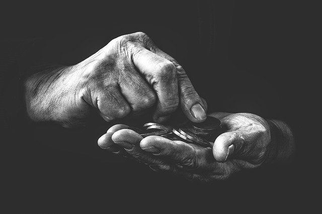 old persons hand holding coins