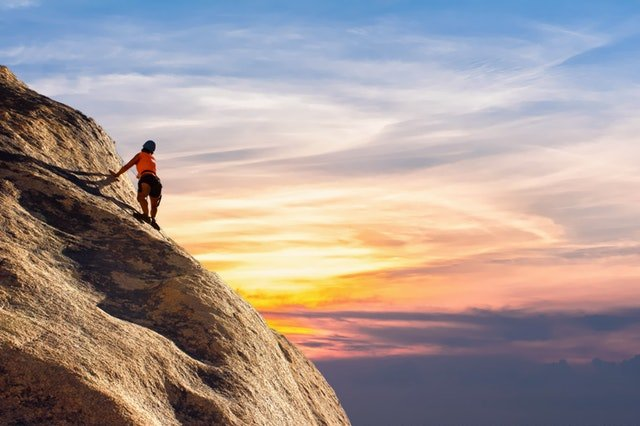 climber climbing on a stone