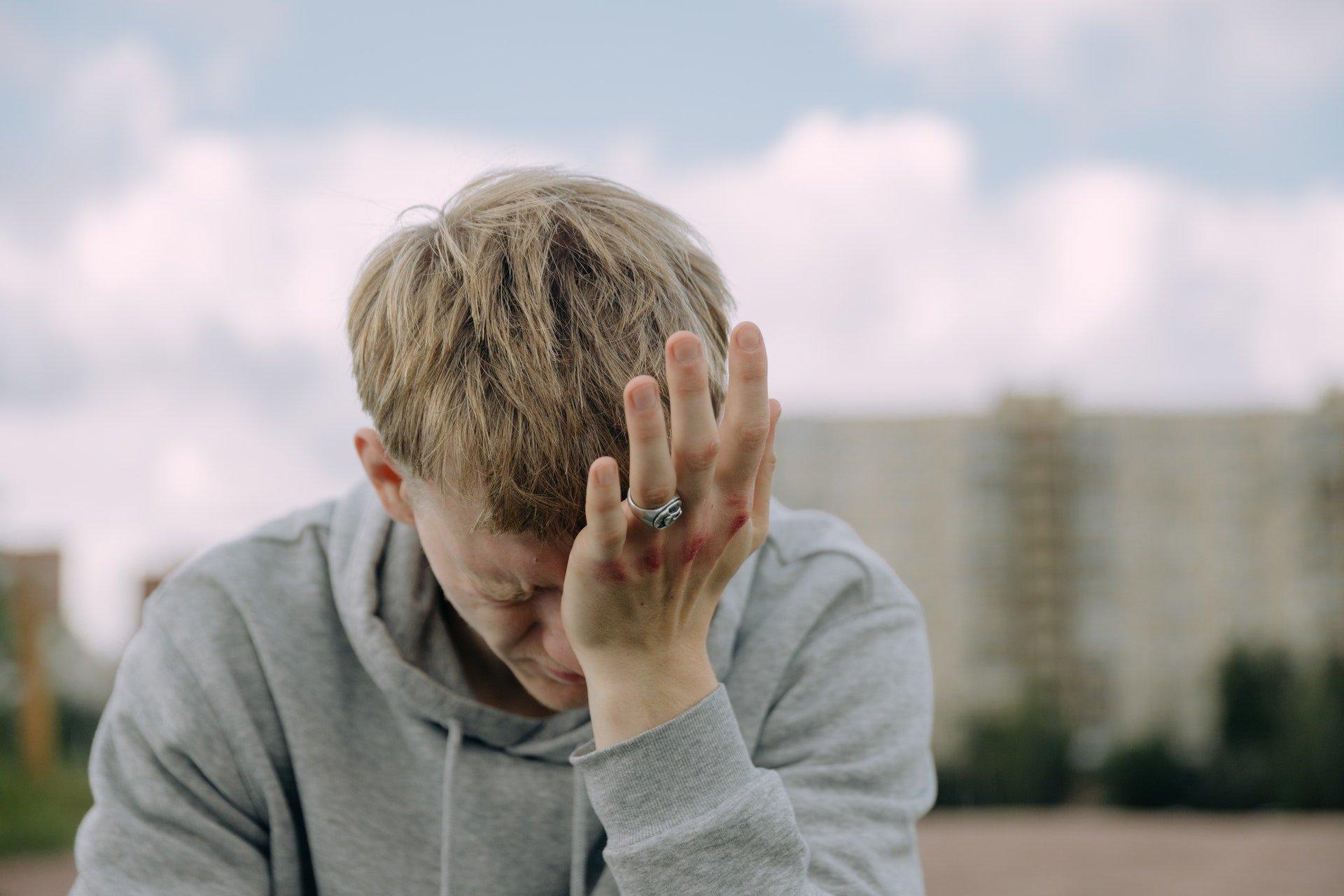 boy crying rubbing his eyes