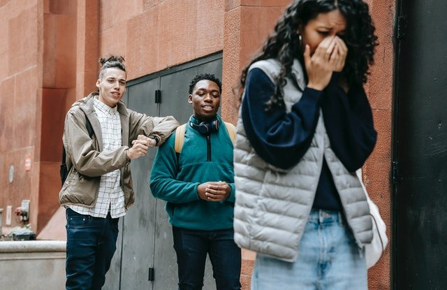 Diverse young men bullying crying ethnic lady