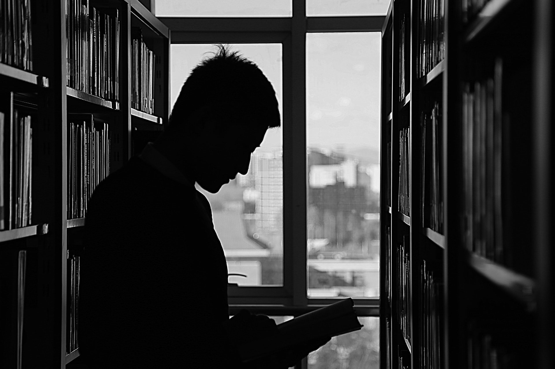 Silhouette of man reading a book in a library
