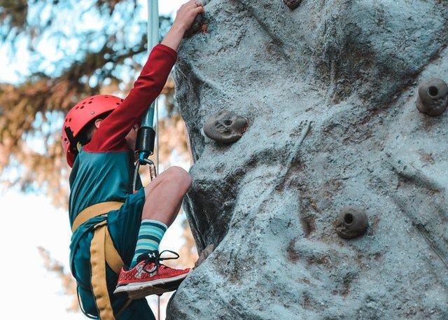 person climbing on gray rock