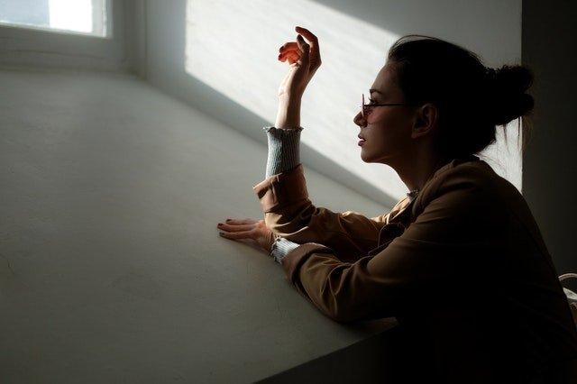 woman leaning on white wall near window