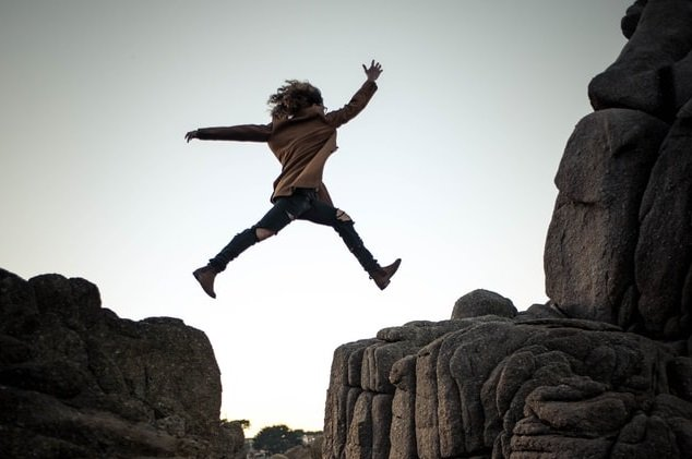 woman jumping through rocks