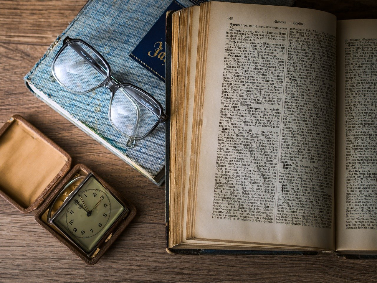 book, glasses and compass on a table