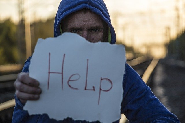 man holding a paper with HELP written on it