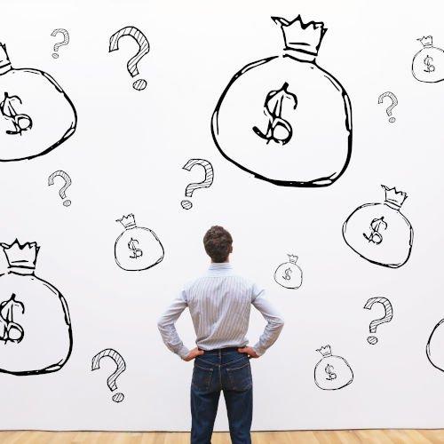 man looking at a wall with money bag graffiti