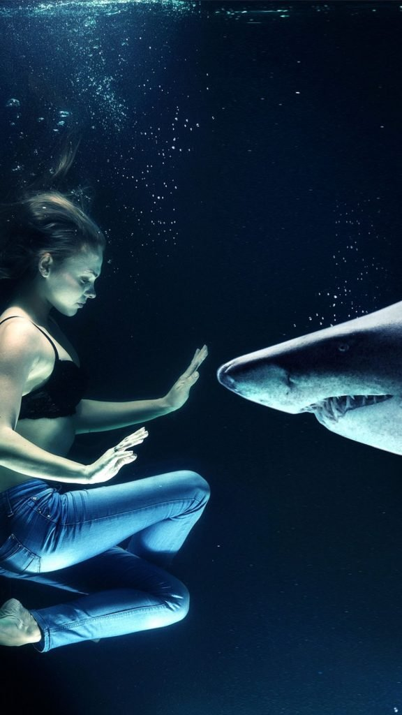 woman trying to hold a shark