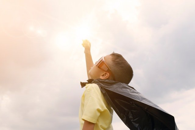 boy wearing cape and glasses raising his hand upwards