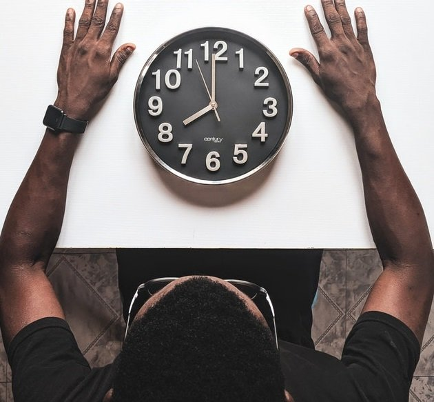 man looking at the black clock on the table