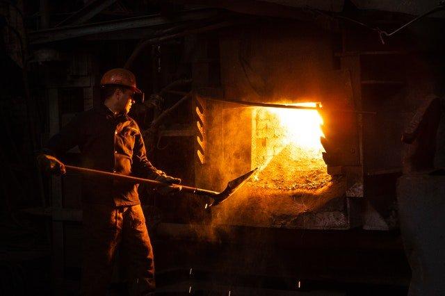 man holding shovel facing a furnace
