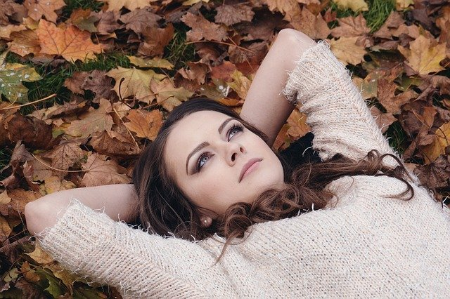 woman lying on leaves looking above
