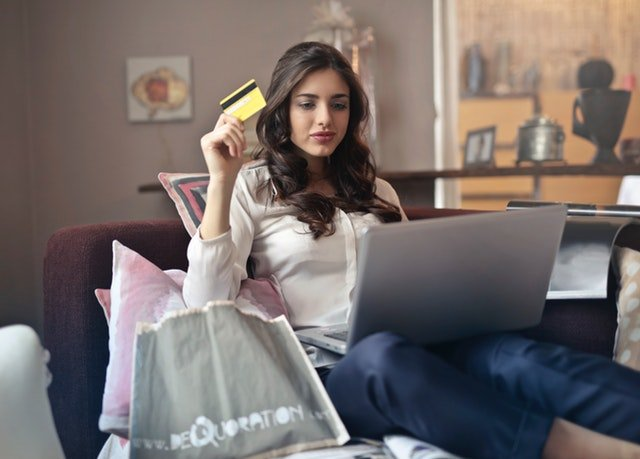 woman holding her credit card looking at her laptop