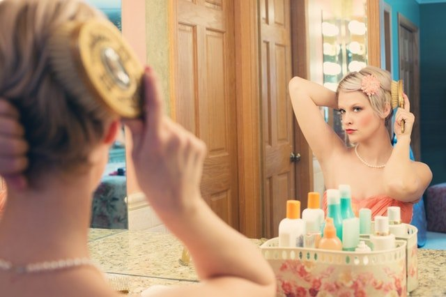 woman using hair brush facing a mirror