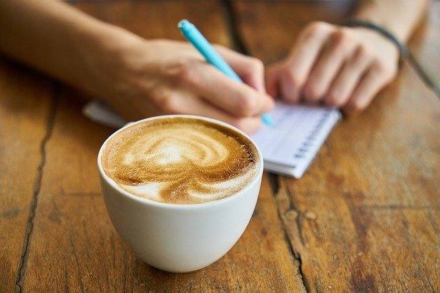 person writing with coffee on the table