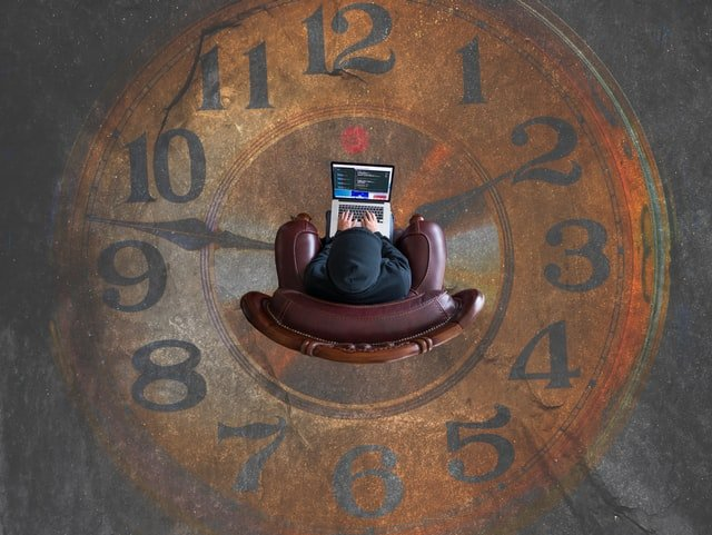 man working and sitting at a big clock