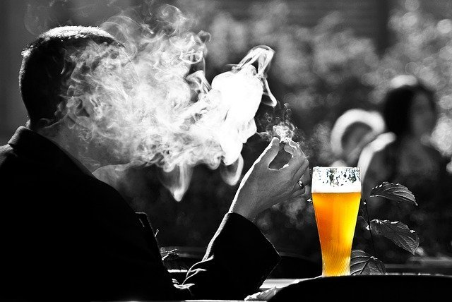 man smoking and drinking beer