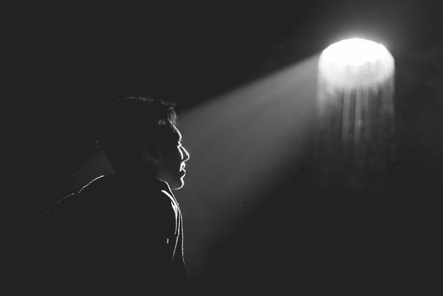 man facing a small light