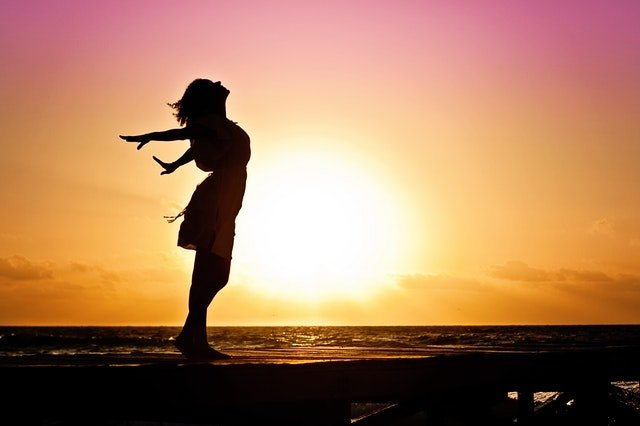 woman stretching in front of a sunrise