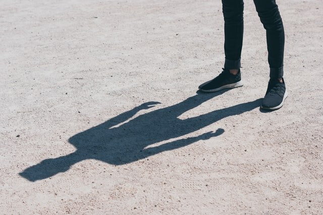 man standing leaving a shadow on the ground