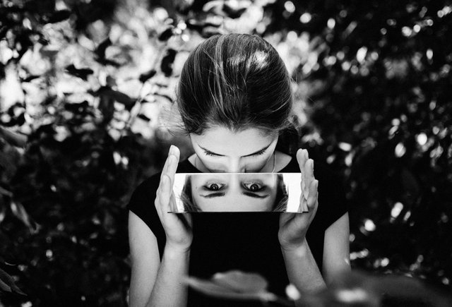 woman watching her reflection on a small mirror