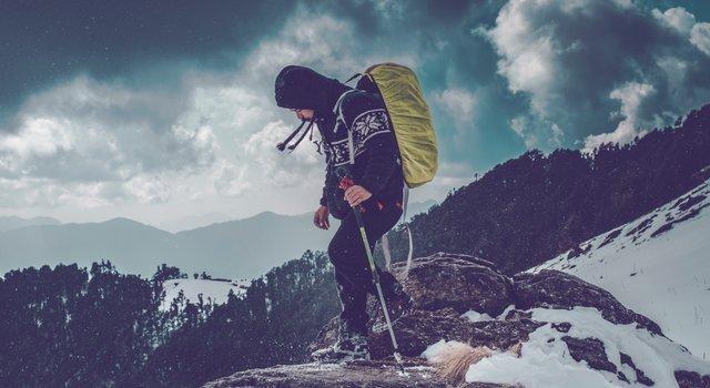 man climbing a mountain with snow